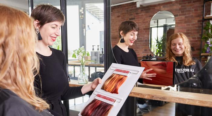Jule Köpp zeigt einer Kunden eine Auswahl von passenden Haarfarben