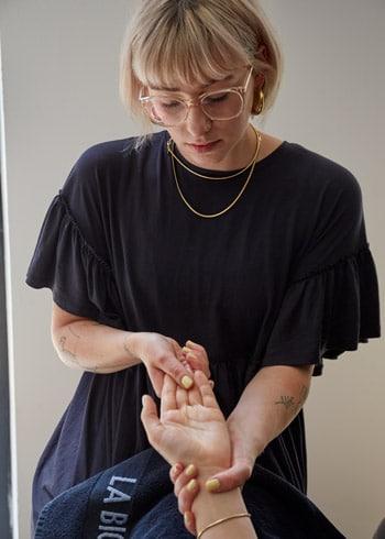 Lea Schaksmeier während einer Handmassage an einer Kundin